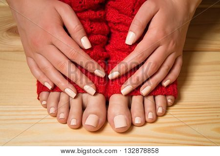 Beautiful beige pedicure and manicure. Legs in red knitted socks on a wooden floor