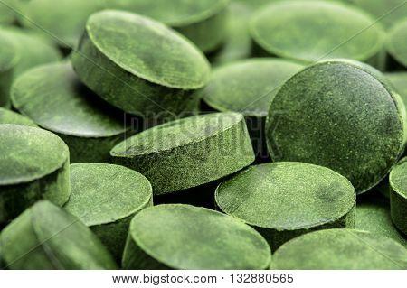 Spirulina green pills (superfood) as background .
