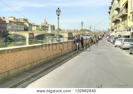 FLORENCE ITALY - October 07.2011: Tourists and townspeople walking on the embankment along of the river Arno in city Florence