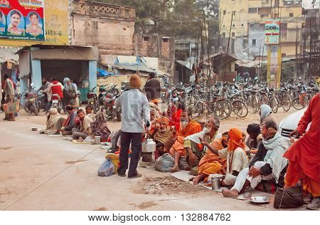 VARANASI, INDIA - JANUARY 2, 2016: Poor people waiting for charity distributing food on the dirty streets of indian city on January 2, 2016. Varanasi urban agglomeration had a population of 1435113