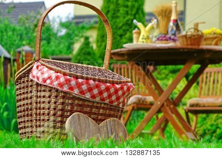 Close-up Of Picnic Basket With Checkered Cloth On The Lawn