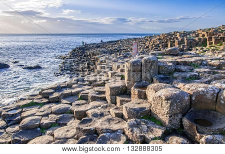 Antrim, Northern Ireland, UK - August 3, 2015: Giants Causeway unique geological hexagonal formations of volcanic basalt rocks on Atlantic coast in County Antrim Northern Ireland in sunset light. UNESCO World Heritage Site