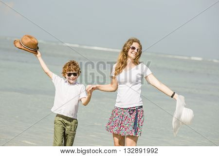 Yound caucasian mother and son having great family time on tropical beach on vacation