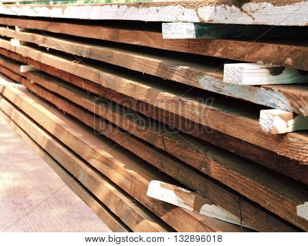 Stack unplaned thick planks covered with antiseptic preparation