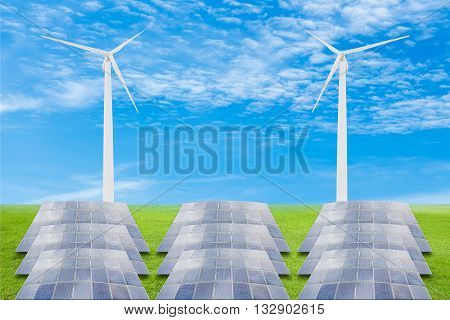 Solar panels and wind turbine on green grass field against blue sky backgrounduseful for carbon credits concept.