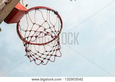 red high basketball hoop in outdoor basketball field playground with nice blue sky.