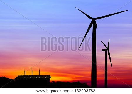 Carbon credits conceptsilhouette wind turbine generator with factory emissions of carbon dioxide on sunset background