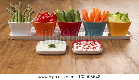 Side view of vegetables, asparagus, plum, cherry, tomatoes, cucumbers, carrot sticks, baby lettuce and yogurt dips on a wooden table