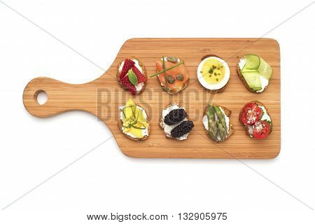 Top view of bite size crostinis on a wooden serving board. Party food crackers isolated on white.