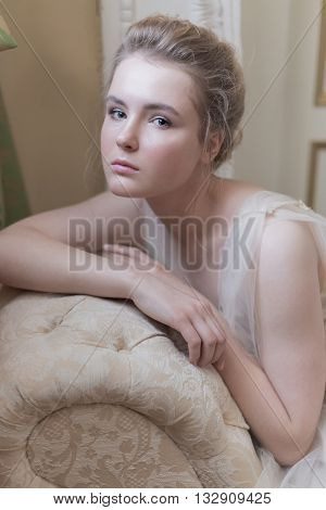 gentle portrait of a young beautiful girl in a light chiffon dress with light make-up and hairstyle sitting on the couch photos in gentle tones in the style of fine art