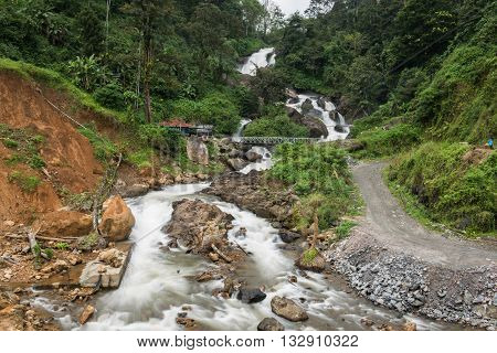 A beautiful and enchanting hilly waterfall flowing down its course through forests and rocks in Kallar Vattiyal, Kochi. A bridge is also seen on the waterfall from distance.