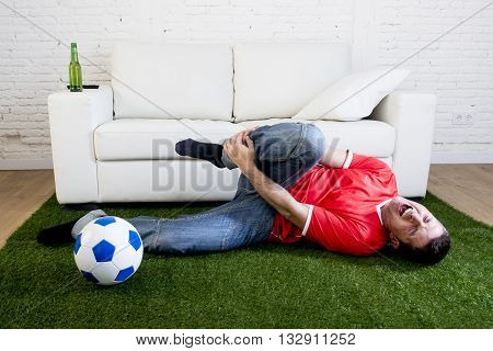 fanatic football fan lying on green grass carpet emulating soccer stadium pitch mocking player in pain hurt on ankle while watching game on television in crazy supporter parody concept