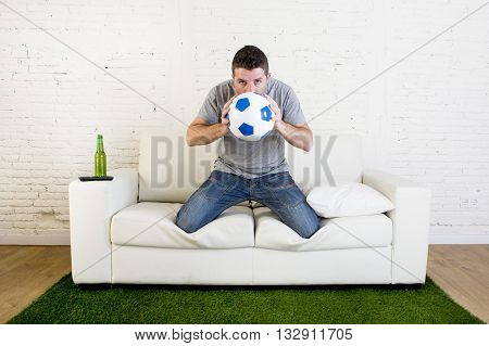 crazy football fan cheering watching television soccer match suffering stress nervous and excited kissing the ball hoping luck on sofa couch with grass carpet emulating stadium pitch