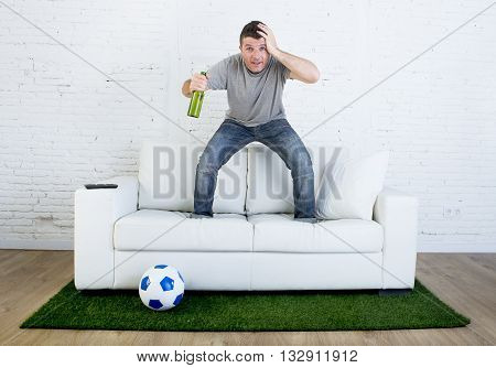 crazy football fan cheering watching television soccer match suffering stress nervous and excited jumping on sofa couch with grass carpet emulating stadium pitch