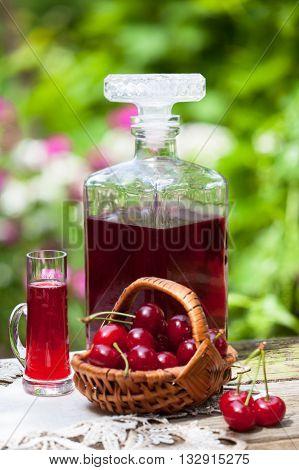 Glass of cherry brandy liqueur with fresh maraschino cherries in the basket