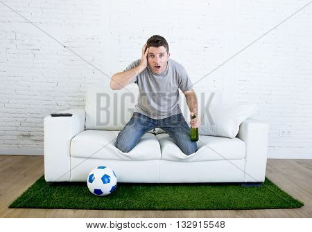 stressed football fanatic fan watching game on tv nervous in disbelief face as if disaster comes holding beer at home couch in grass carpet and ball emulating stadium pitch