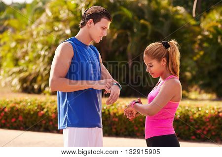 Young people doing sport activities girl and friend running using fit watch man and woman jogging on the street. Concept of eisure health recreation fitness exercising training workout