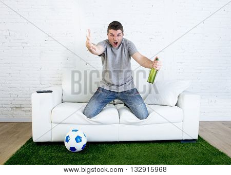 angry football fanatic fan watching game on television holding beer gesturing upset and crazy angry complaining and screaming at home couch on grass carpet with ball emulating stadium pitch