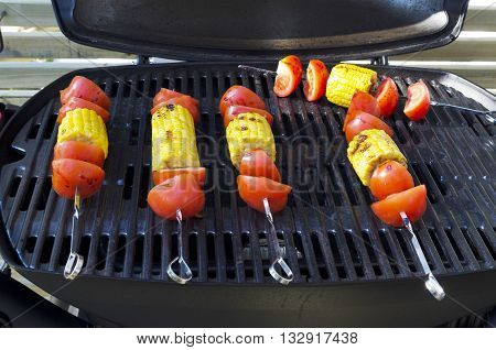 Skewer with corn cobs and tomatos on the grill photo from the North of Sweden.