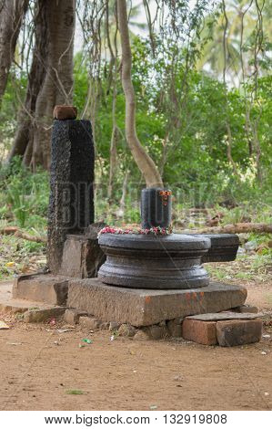 Chettinad India - October 17 2013: Closeup of black Shivalingam standing in vulva in a forest shrine near Kothamangalam. Foreground brown dirt. Background green forest.
