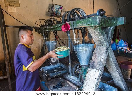 SUCHITOTO EL SALVADOR - MAY 07 : Salvadoran man work at a Corn tortilla dough factory in Suchitoto El Salvador on May 07 2016. Corn has been a staple food in Central American cultures since pre-Columbian times