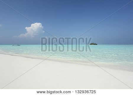 Maldivian island abd boat in turquise water with white sand