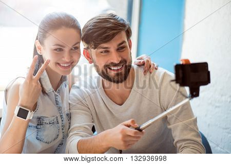 Taking a photo. Smiling and cheerful modern young woman and man sitting in a cafe and using a smartphone and a selfie stick to take selfie photograph