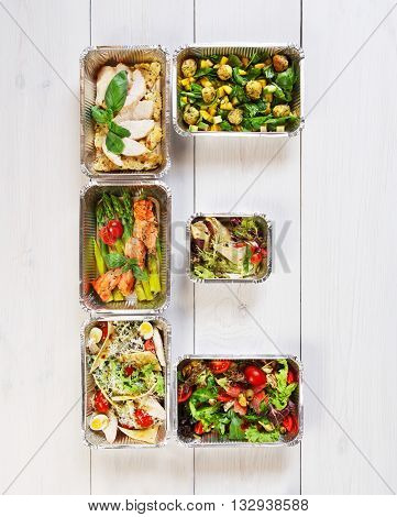 Ecological food. Eco friendly organic food concept, e letter made from dishes in aluminium lunch boxes. Food take away, healthy food delivery. Fitness meal, salads top view, flat lay at white wood