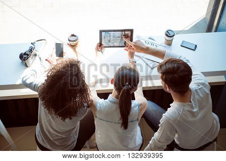 Lifestyle and technologies. Cheerful modern young women and man sitting together in a cafe while drinking coffee and using their digital tablet and cell phones during their leisure time