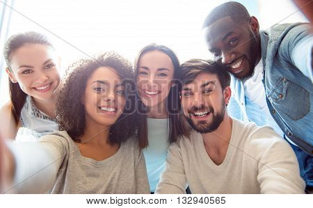 Friends forever. Positive and merry modern young people sitting together and  taking a  selfie photograph while being in a friendly mood