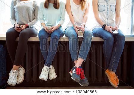 Using mobile phones. Cropped picture of modern young women using their cell phones while sitting on a window sill and typing messages