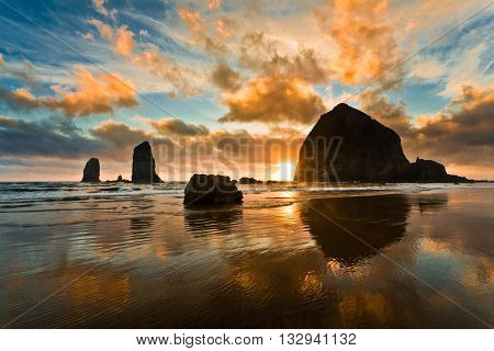 Quiet summer sunset at Cannon Beach, Oregon, USA: colorful clouds, sky reflection in the water.