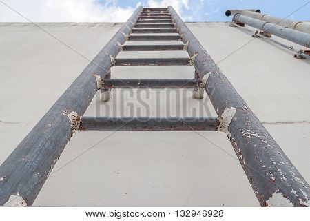 Old vertical industrial metal rusted ladder. Staircase to blue sky with clouds no safety rails.