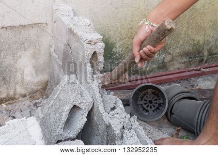 hammer in hand breaking brick wal : young power use Hammer smash a brick wall In construction : select focus Hammer Blur blurred background.