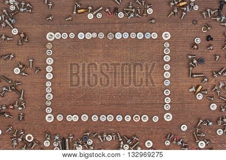 small fixing screws scattered on a wooden board in the center are the space for an inscription limited is used by screws as a background