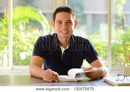 Smiling man opening book on the table about to read