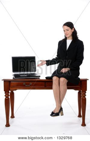 Female Executive Sitting On Desk, Gesturing To Open Laptop (Ss)