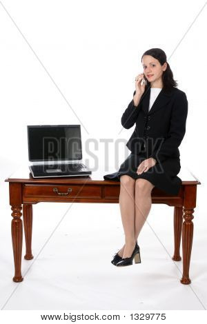 Young Executive Sitting On Desk With Laptop And Cell Phone (Ss)