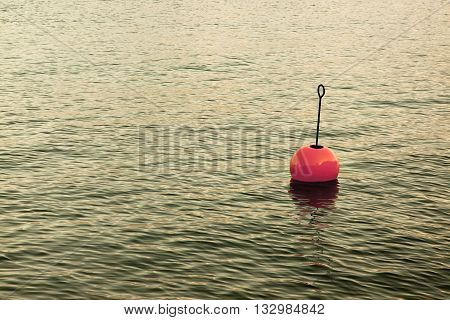 Red bouy on a calm lake - toned image with copy space