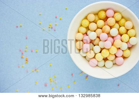 Confectionery food background beautiful sugar bubble sprinkle mix on blue background selective focus blank space for text top view poster