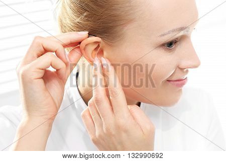 Young woman assumes a hearing aid .