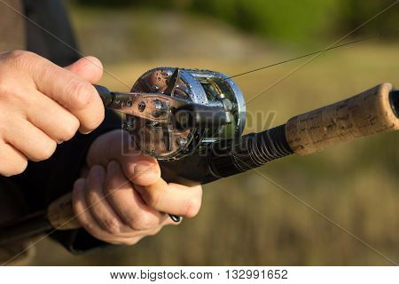 Man fishing with reel and rod. One hand on the crank and reeling fishing line in to the round reel and other hand holding fishing rod with blurred nature background.
