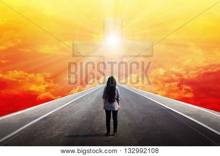 Back or rear view women standing on road meet big crucifix or cross at the end with light shining from golden sky light from god through crucifix or cross on heaven sky women and highway to god sky with crucifix light