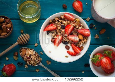 Granola. Granola with yogurt honey and berries on blue wooden table.