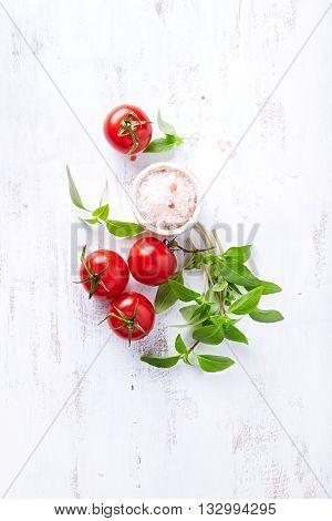 An arrangement of tomatoes, basil and himalayan salt