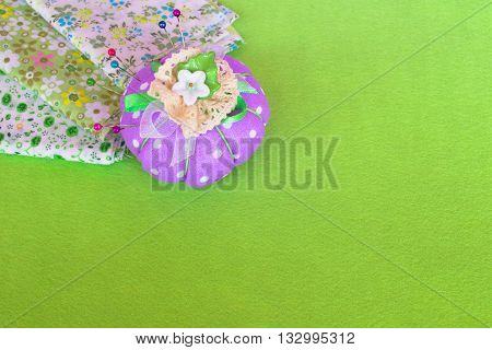 Pin cushion with pieces of cloth on the green felt