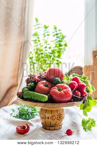 Still life of fresh vegatables in a wooden plate on lite background