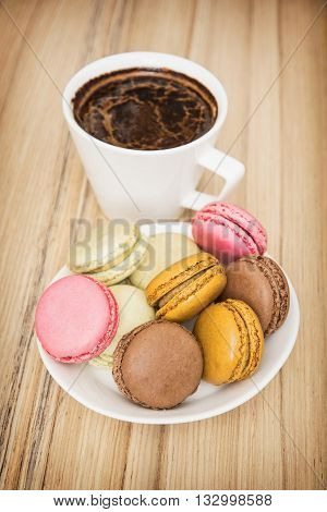 Cup of black coffee with french colorful macarons. Sweet delight. Food and drink. Vertical composition. Tasty macarons.