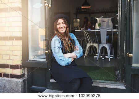 Smiling Worker Sitting In Coffee House Doorway