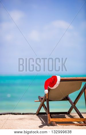 Red santa hat on chair longue at tropical caribbean beach